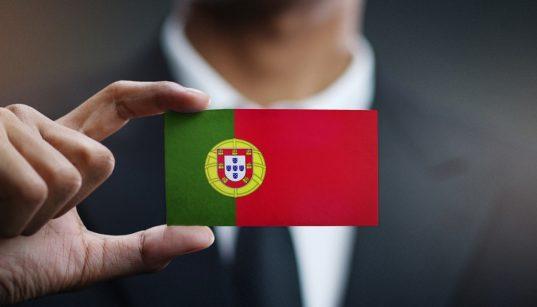 homem segurando cartão com a bandeira de portugal