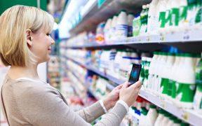consumidor com celular olhando produto na prateleira do supermercado