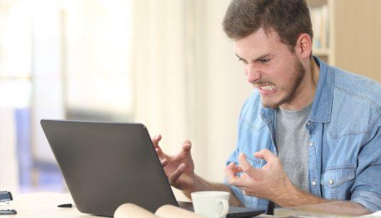 funcionario furioso trabalhando no computador