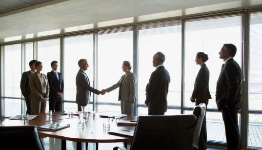 executivos dão as mãos para fechar negocios