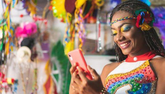 mulher jovem com celular no carnaval