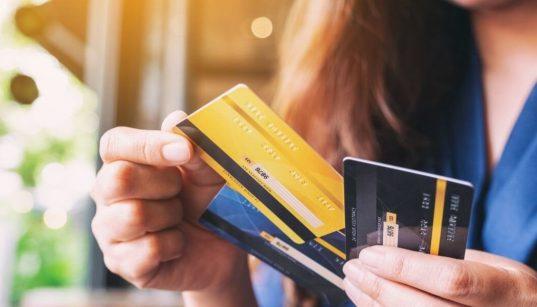 mulher segurando cartões de credito