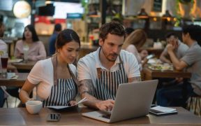 cafeteria com empreendedores no computador e clientes ao fundo