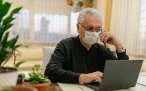 consumidor idoso com mascara e usando smartphone e computadorfala