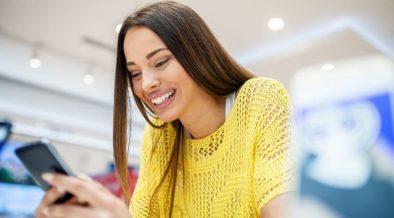 consumidora com celular dentro da loja