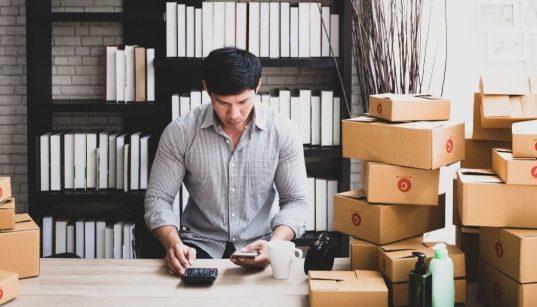 empreendedor fazendo calculos em meio a caixas de produtos na empresa