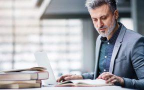 executivo estudando com livros e computador