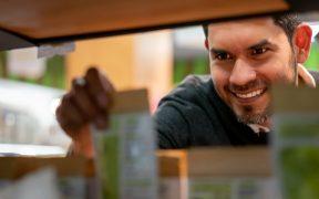 homem pegando produto na prateleira do supermercado