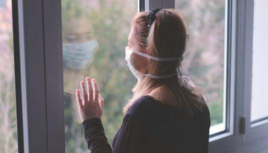 mulher com mascara olhando na janela