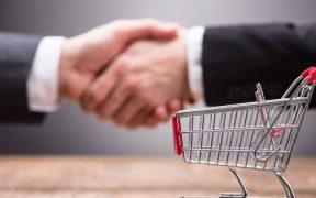 carrinho de supermercado e ao fundo homens de enegocios apertando as mãos