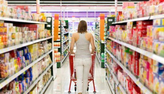 consumidora andando com carrinho no corredor do supermercado
