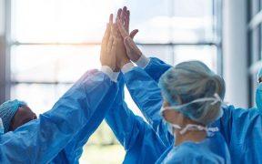 equipe de medicos no hospital unindo as mãos comemorando