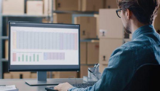 homem usando computador dentro de um armazem de produtos