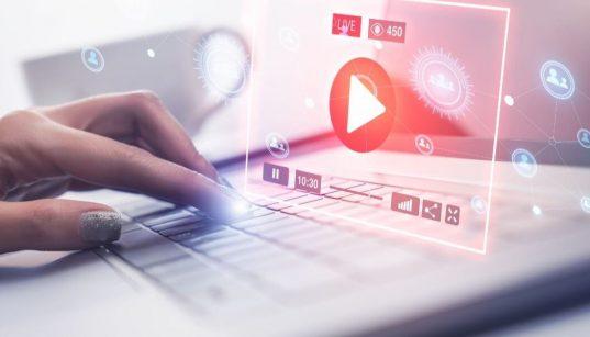 mao femininca no computador acessando um video ou live