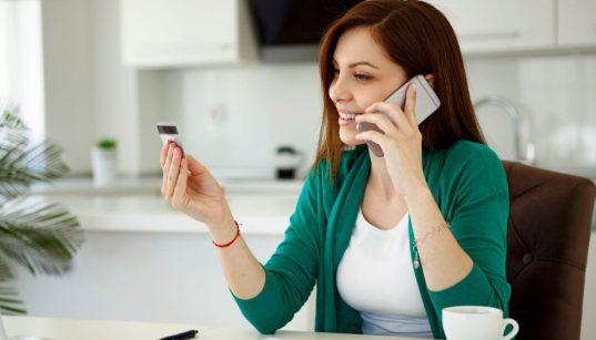 mulher em casa com celular e olhando pra cartão de credito