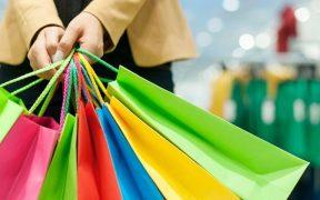 mulher segurando varias sacolas coloridas
