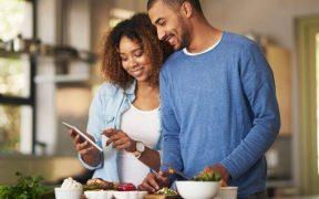 casal preparando comida em casa olhando receita no celular