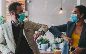 funcionarios se cumprimentam com cotovelo na pandemia da covid