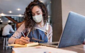 empreendedora estudando online e com caderno