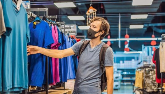 homem de mascara em loja de roupas