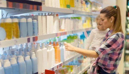 mulher com bebe no colo escolhendo produto no supermercado