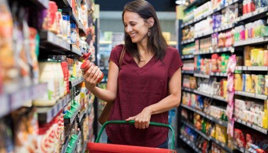 mulher no corredor do supermercado pegando produto na prateleira