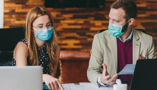 profissionais com mascara analisando negocios covid