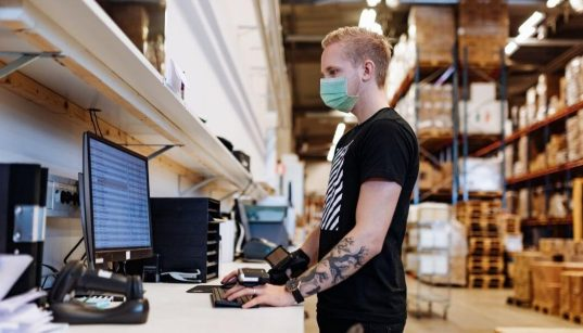 trabalhador com mascara covid em armazem de industria