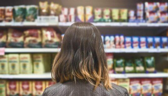 consumidora de costas olhando prateleira de supermercado