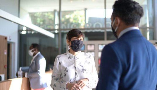 empresarios com mascara conversam no saguao da empresa