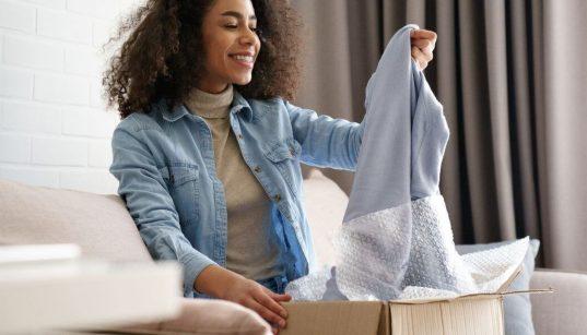 consumidora abrindo caixa com roupa