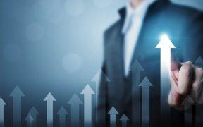 executivo aponta tela com setas que indicam crescimento