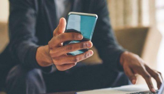 executivo conectado com celular e computador
