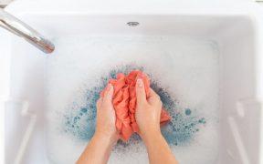 mãos femininas lavando roupa no tanque