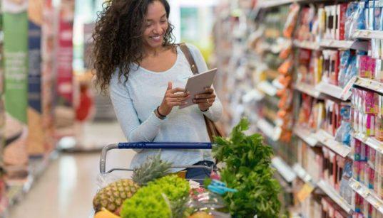 mulher fazendo compra no supermercado e olhando tablet