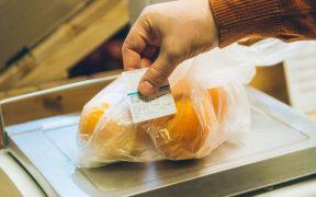 pessoa colando etiqueta em produto em cima da balança no supermercado