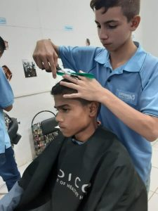 jovem cortando cabelo no curso de cabelereiro cidade dos meninos