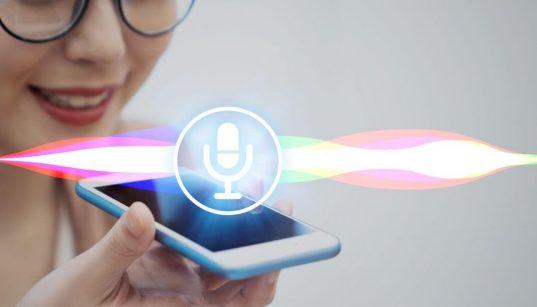 mulher segurando smartphone usando assistente de voz