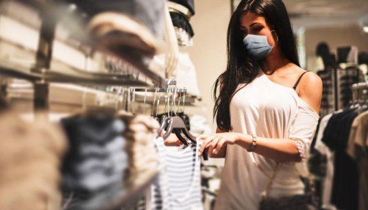 consumidora usando mascara olha roupas em uma loja