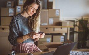empreendedora usando celular em sala com caixas
