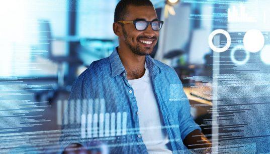 homem olhando para tela com dados de programação