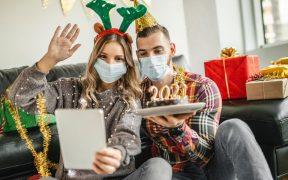 jovem casal comemorando ano ano com mascara e fazendo chamada de video