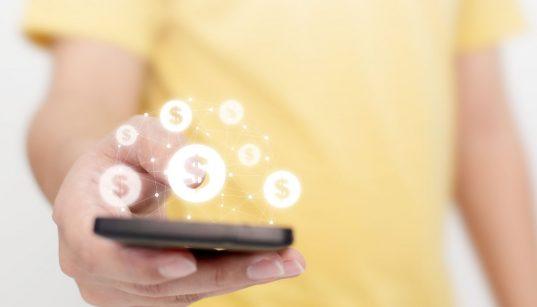 mao masculina usando celular com app de transacao financeira