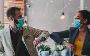 executivos se cumprimentam no escritorio usando mascara